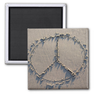 A peace sign drawn in the sand. square magnet