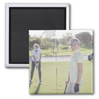 Friends playing golf square magnet
