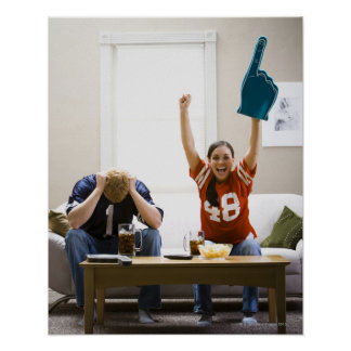 Man and woman sitting on sofa watching football poster