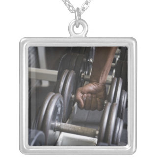 Man taking weight from rack square pendant necklace