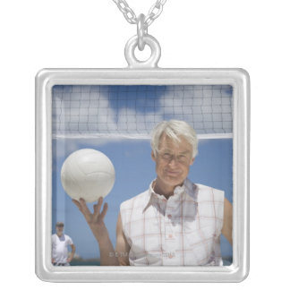 Portrait of mature man holding volley ball on square pendant necklace