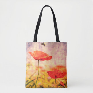 Red poppies and a bumble bee in a summer meadow tote bag