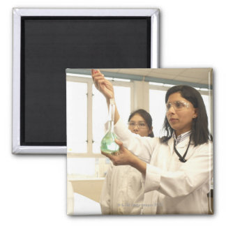 Scientist adding solution to beaker square magnet