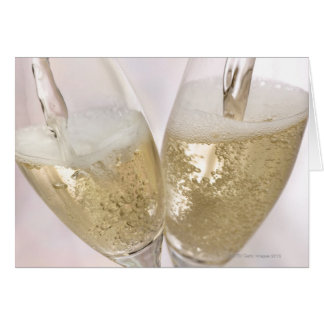 Two champagne flutes being filled with sparkling greeting card