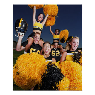 Two cheerleaders riding on shoulders of football poster