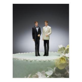 Two groom figurines on top of wedding cake postcard