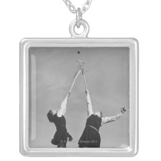 Two lacrosse players jump for the ball. square pendant necklace