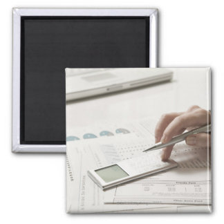 Woman working on financial paperwork and square magnet
