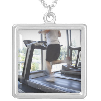 Young man running on a treadmill at health club, square pendant necklace