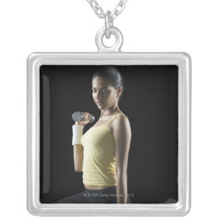 Young woman exercising with dumbbells square pendant necklace
