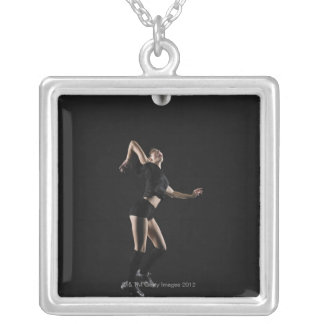 Young woman jumping to hit volleyball, side view square pendant necklace