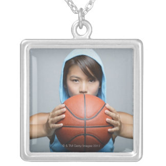 Young woman with basketball looking at camera square pendant necklace